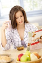 Woman reading a magazine at breakfast table