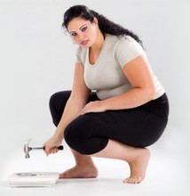 Fat woman breaking weighing scale with hammer