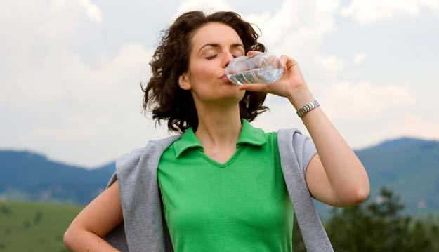 woman drinking water during travel