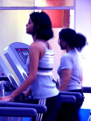 Two girls on a treadmill in a gym