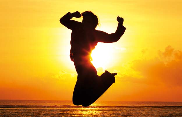 Man jumping against sunrise