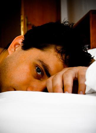 Anxious man lying on bed sleepless
