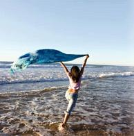 young happy woman dancing on the beach