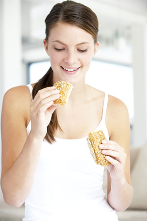 young woman eating a snack bar