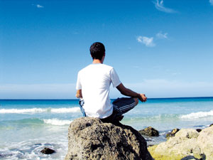 man meditating at the beach