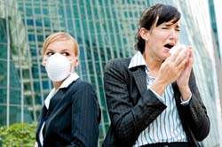 woman sneezing with another woman wearing a mask