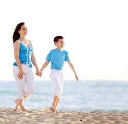 son walking with mom on the beach