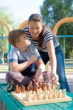 mom teaching chess to her son