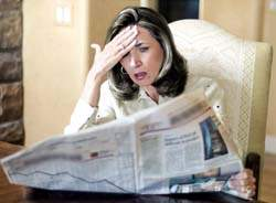 woman disgusted while reading the newspaper