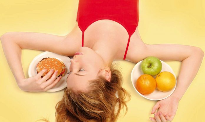 women with fruits on one side and burger on the other