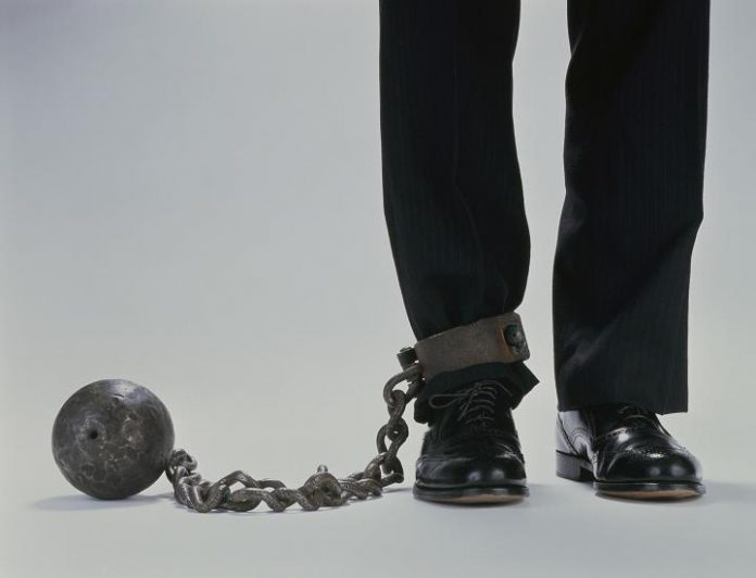 Man's legs chained with a heavy metal ball