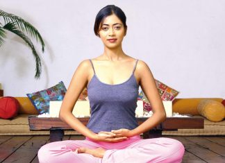 A woman sitting in lotus pose, preparing for chanting mantras