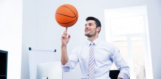 Happy man playing with ball in office