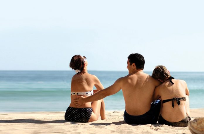 Man with two woman on the beach