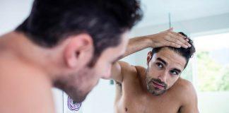 Man looking hair in mirror