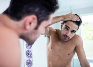 Man looking hair in mirror