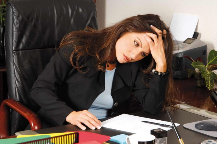 Female Executive stressed out and sitting at her desk massaging her head to relieve a tension headache