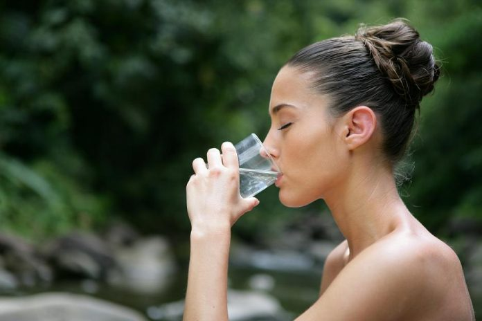 beautiful brunette absorbed in drinking water