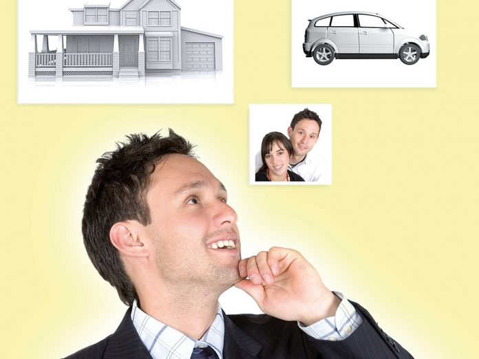 business man with personal goals on the wall: family - car and a house