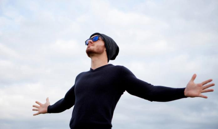 Man looking towards sky with arms outstretched in a gesture of surrender