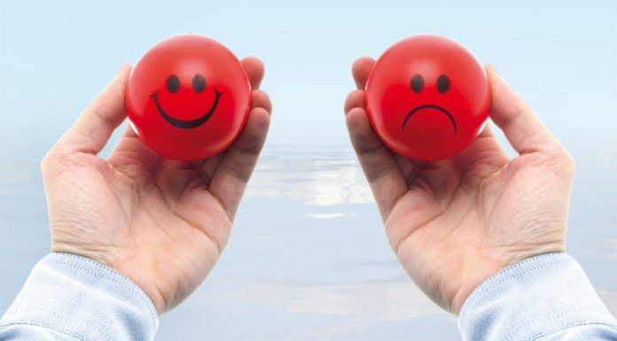 Man with one smiling and other sad stress balls