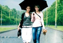 Two girls walking on road in rain