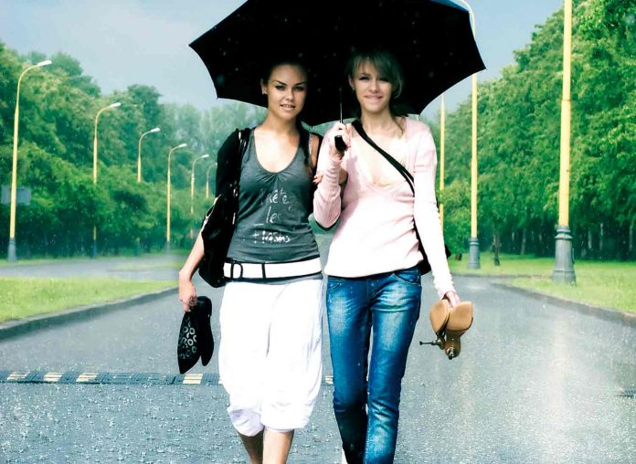 Two girls walking on road in rain