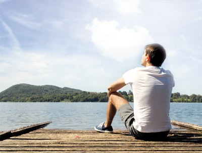 Man sitting near a lake watching the beauty