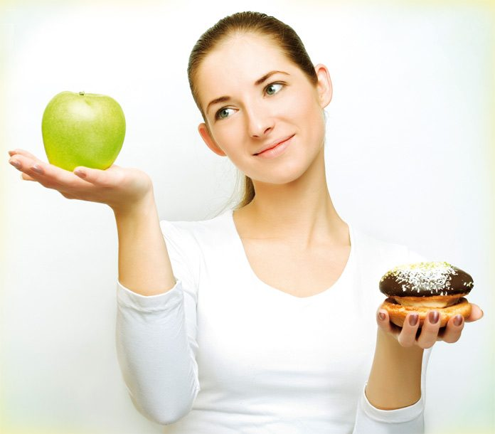 Portrait of pretty young girl deciding what to eat: an apple or burger