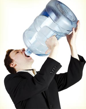 man drinking from big bottle of water