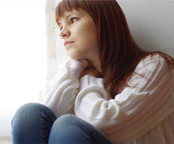 A sad young woman staring outside the window