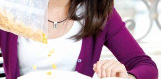 Woman having corn-flax with tea