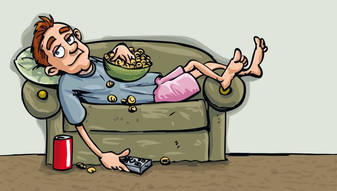 Lazy man lying on sofa, eating and watching TV