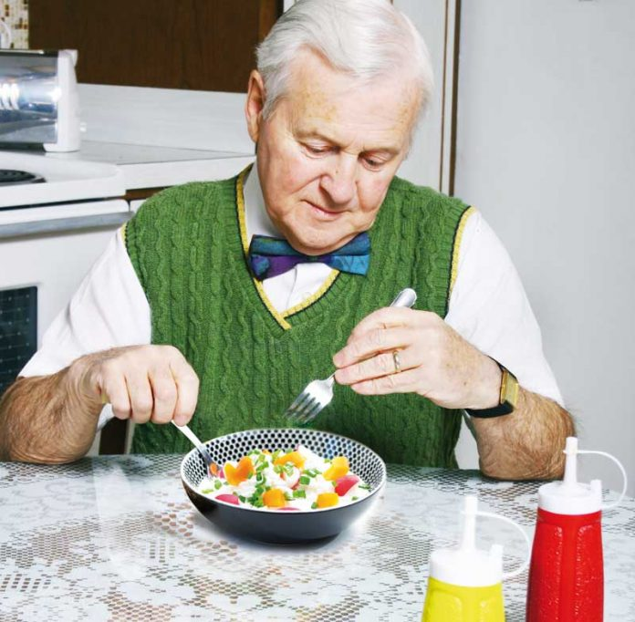 elderly man having meal alone on the table