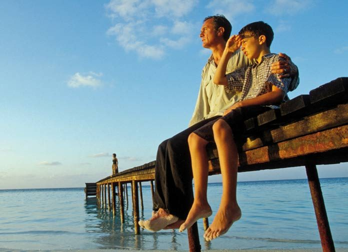 boy with his father sitting on a sea shore