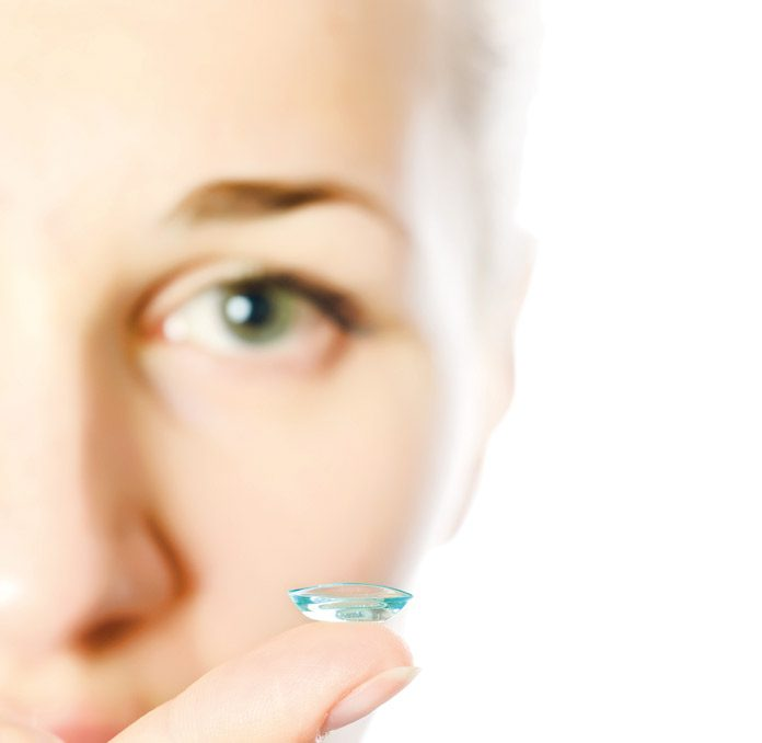 woman holding contact lenses