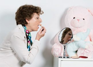 mature woman applying lipstick