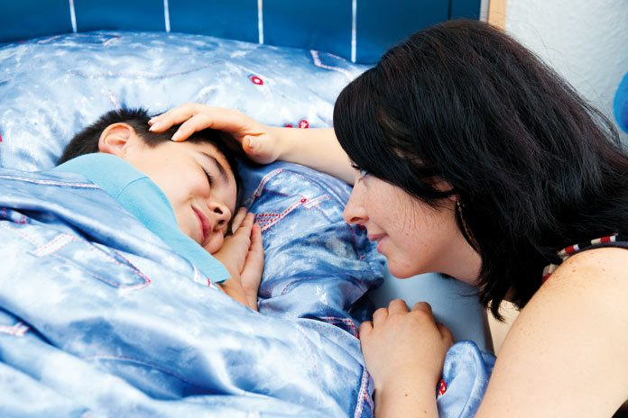 mother putting her son to sleep