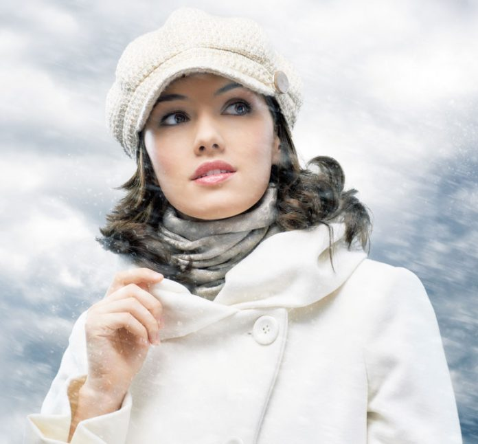Woman wearing sweater, cap