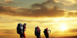 Group trekking on hill at sunset