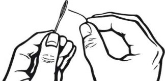 hands trying to put a thread through the eye of a needle