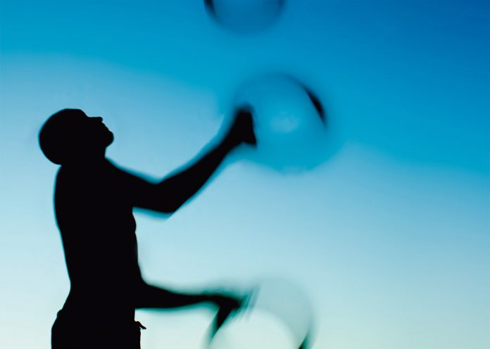 Silhouette of a man juggling rings