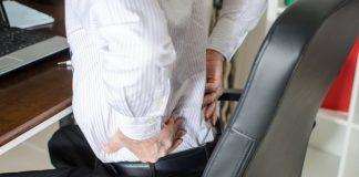 man having back pain in office
