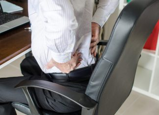 man having back pain in office