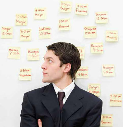 Man looking at all his schedules written in post-it