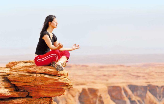 Woman doing meditation on rock
