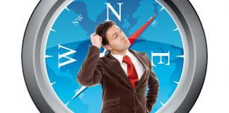 Man thinking standing in front of compass