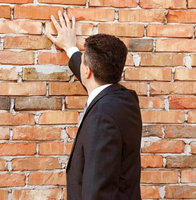 Man touching the bricks of the wall