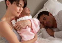 Woman holding her newborn baby / gloom after childbirth