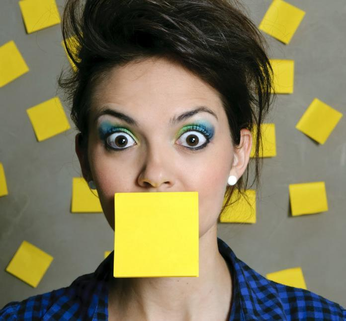 Woman with a post-it on her mouth